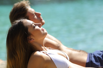 Relaxed couple sunbathing on the beach on vacation