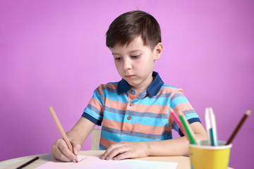 European boy carefully drawing with colorful pencils at home.