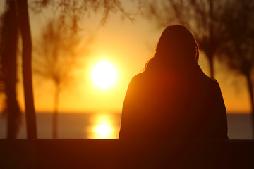 Silhouette of a lonely woman watching sunset in winter Wall mural