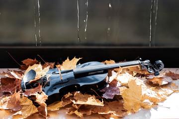 Schwarze Geige in Ahornblättern auf der Fensterbank