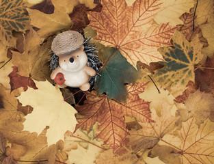 Zierfigur eines Igels sitzt in einem Blätterhaufen.