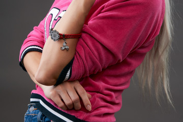 Woman fashion model body part portrait isolated on dark background. Beautiful teen girl in casual clothes, denim jeans and pink pullover jersey sweater and hipster fashion bracelet on hand, close-up