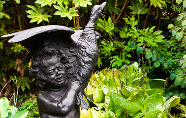 a statue of child with duck with plants in the background