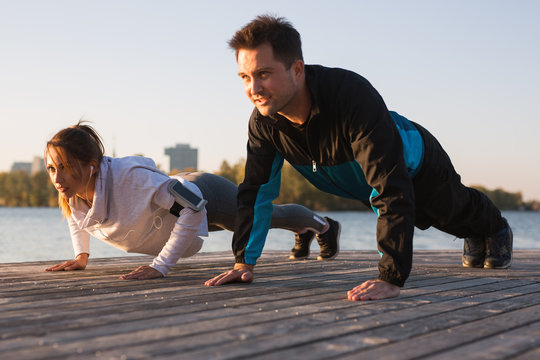 Beautiful young couple working out outside