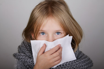 cute blond hair little girl blowing her nose with paper tissue. Child winter flu allergy health care concept