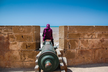 Essaouira -  woman sitting on an old cannon
