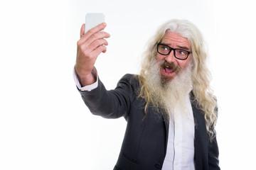 Studio shot of senior bearded businessman taking selfie picture