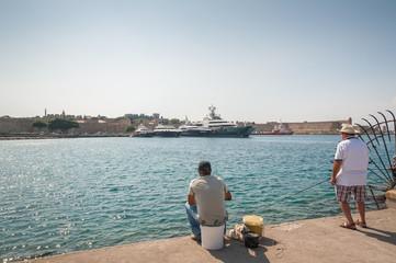 Two fishermen at Akti Sachtouri sea promenade. Rhodes, Old Town. Island of Rhodes, Greece. Europe.