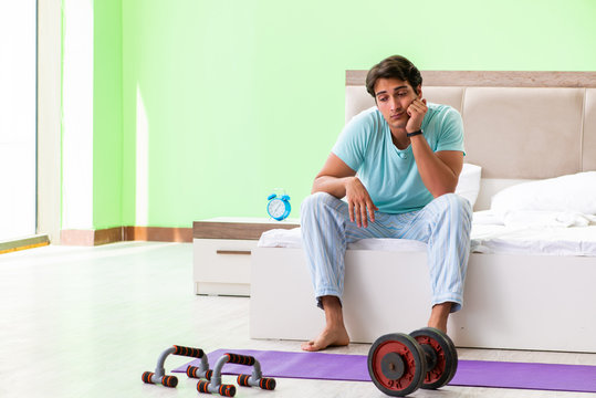 Young man in pajamas doing morning exercises