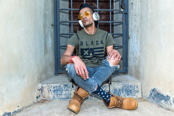 Extravagant (hipster) male model with sunglasses, headphones and a black hat. The model poses next to the door with grids.