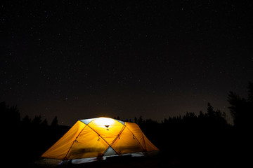 A tent lit up at night with trees and the stars above