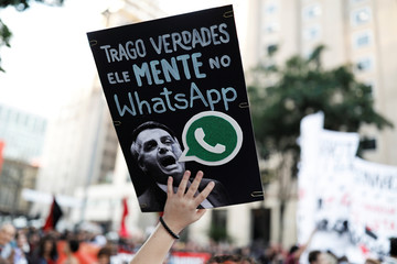 Woman holds a sign with the image of presidential candidate Jair Bolsonaro during a protest in Sao Paulo