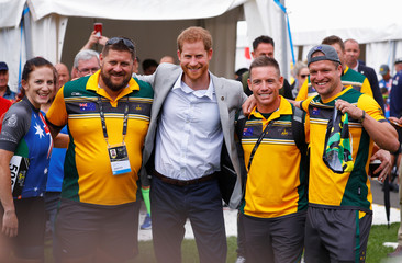 Britain's Prince Harry poses for a photo with Australian athletes taking part in the Invictus Games at the Royal Botanic Garden in Sydney