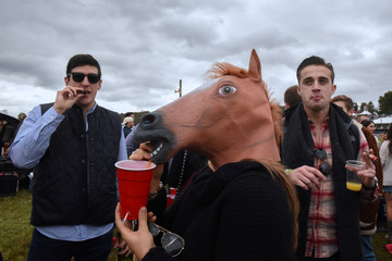 A person wearing a horse mask stands with two men during the 98th Running of the Far Hills Race Meeting at Mooreland Farm in Far Hills