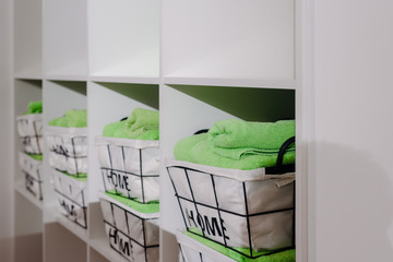 Clean green towels on shelves in modern fitness center