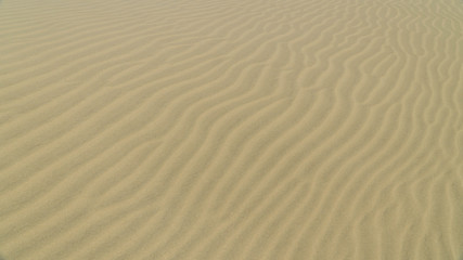 View of sand dune surface with undulated wave patterns former by wind, New Zealand
