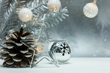 decorative glass star, silver cone and christmas jingle bells on blurred grey background with fir tree branch and garlands