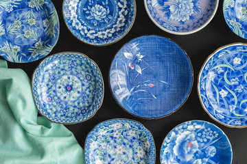Blue and white decorative Japanese plates on black background - Top view photo