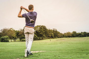 Back of golfer hitting ball on green field with copy space.