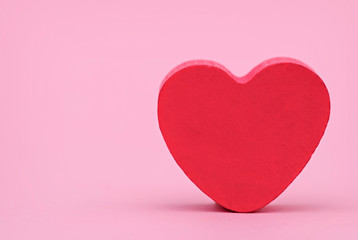 Red heart on a pink background, front view