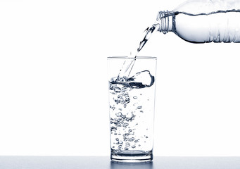 Pouring drinking water from bottle into glass on white background