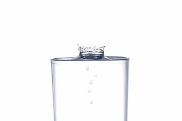 Water drop splash on drinking glass on white background