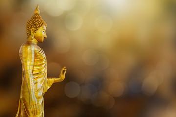 Ancient golden Buddha statue on blurred golden bokeh background