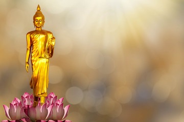 Golden Buddha statue on pink lotus on  blurred golden bokeh background