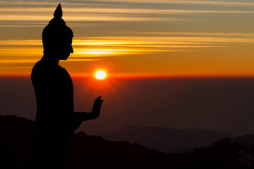 Silhouette of Buddha statue on blurred golden sunrise background