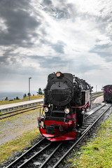 Black locomotive with red color driving on a railtrack