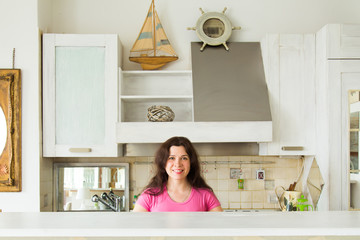 Housewives, emotions and people concept - Happy young woman in the kitchen at home