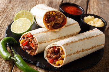Mexican popular grilled burrito snack with beef and vegetables and with sauces close-up. horizontal