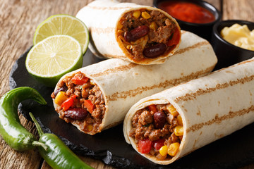 Fast food grilled burrito with beef and vegetables close-up on the table. horizontal, rustic