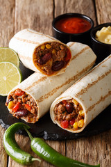 Mexican grilled burrito with beef, beans, corn, pepper and tomatoes served with sauces close-up. vertical