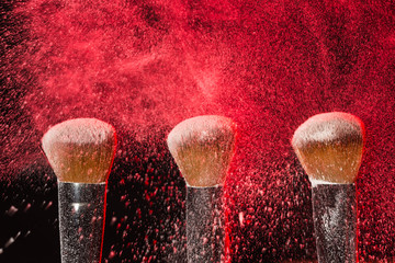 Make up, beauty, mineral cosmetic concept - powder brush on black background with red powder splashed on it