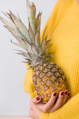 Closeup of juicy pineapple in girl's hands against the background of a yellow sweater. Healthy food concept
