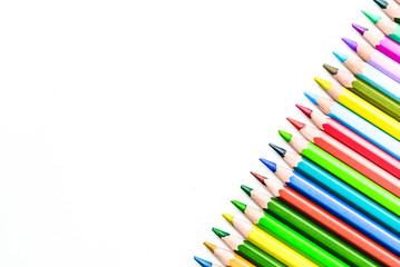 colored pencils in a row on a white background