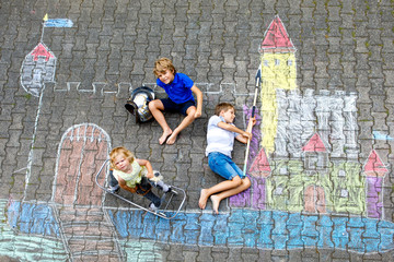 Two little kids boys and cute toddler girl drawing knight castle with colorful chalks on asphalt. Happy siblings and friends having fun with creating chalk picture and painting
