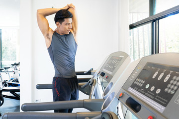 Young handsome man stretching hands in fitness club. Cardio workout, guy warming up, preparing for running on treadmill. Healthy lifestyle, guy training in gym, copy space