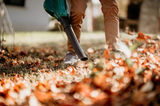 Gardener using leaf blower, vacuum and working in garden