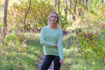 Photo portrait of a beautiful blonde girl in the park on the nature in the forest.