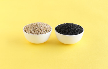 Healthy food white and black sesame seeds, rich in essential nutrients and high oil content, in bowls.