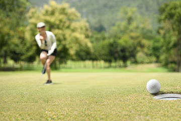 Woman golfer cheering after a golf ball on a golf green