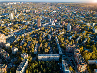 Aerial view of landscape with a large number of residential buildings on the outskirts of the city on an autumn day during the Indian summer with the road and cars