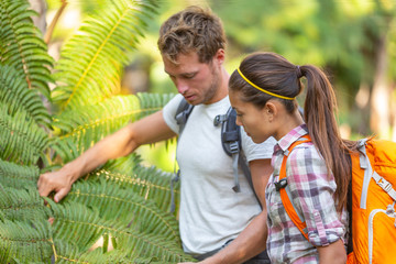 Nature guide biologist naturalist botanist teacher teaching to student about plants and biology. Interpretive walk in rain forest, hiking people studying with backpacks.