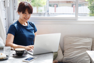 Smiling woman watching video on laptop computer in cozy coworking interior, female student rest during free time reading news blogging in social networks using netbook.