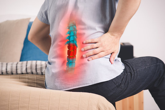 Pain in the spine, a man with backache at home, injury in the lower back