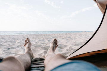 Man relaxing in a tent in front of sea.