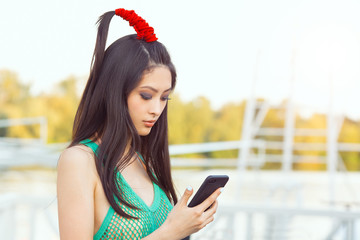 Happy young Asian woman with smartphone standing outdoors in city park. . Young Asian casual girl using her mobile phone app 4g data while relaxing on summer vacations. Fashion photo of gorgeous