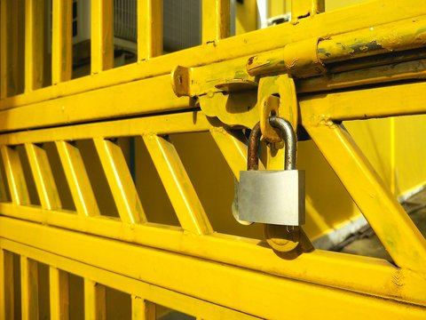 Selective focus of rusty padlock and door latch on yellow steel gate door in construction and safety concept